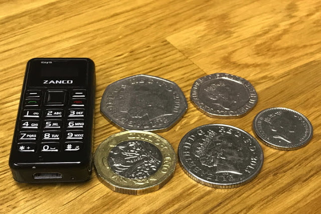 The image shows Zanco Tiny t1 placed on a table along with some coins to compare its size and give an idea of the tiny dimensions of the phone to the users